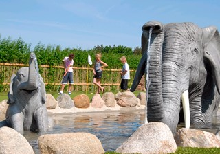 Kids playing Adventure Golf among elephants