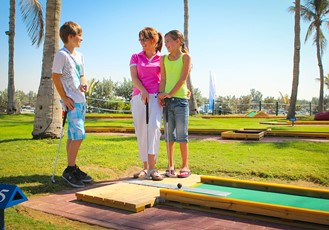 Family playing mini golf